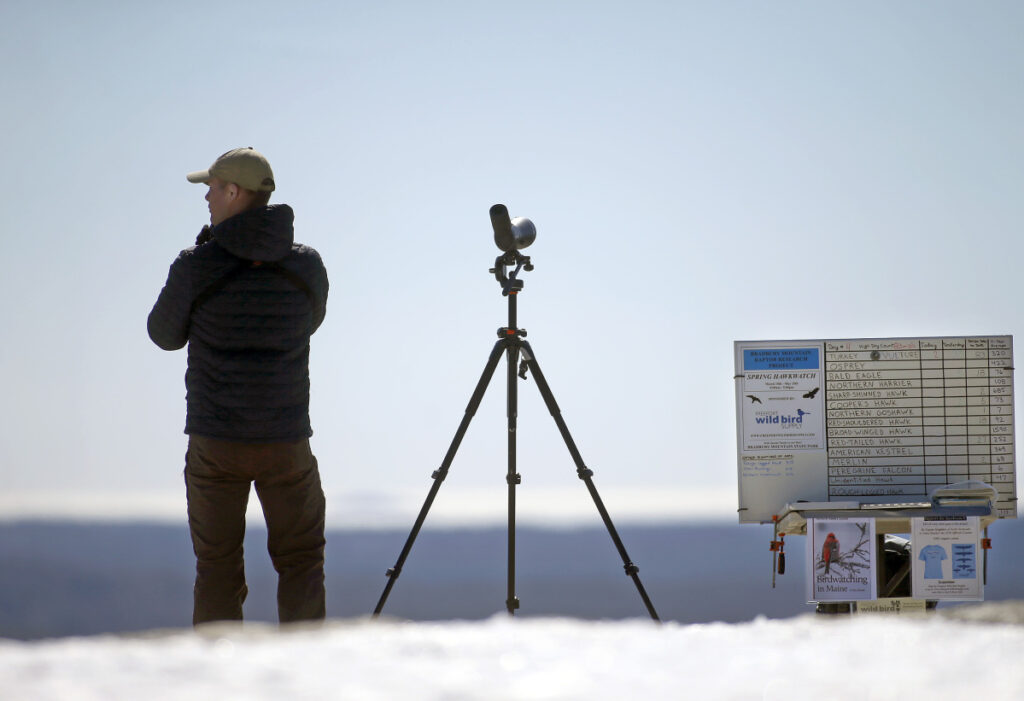 Zane Baker scans the skies for migrating raptors as part of the annual Bradbury Mountain hawk watch. He uses a combination of the naked eye, binoculars and a high-powered scope to find the birds, often spotting them miles away. He keeps track of the sightings on a dry-erase board, right.