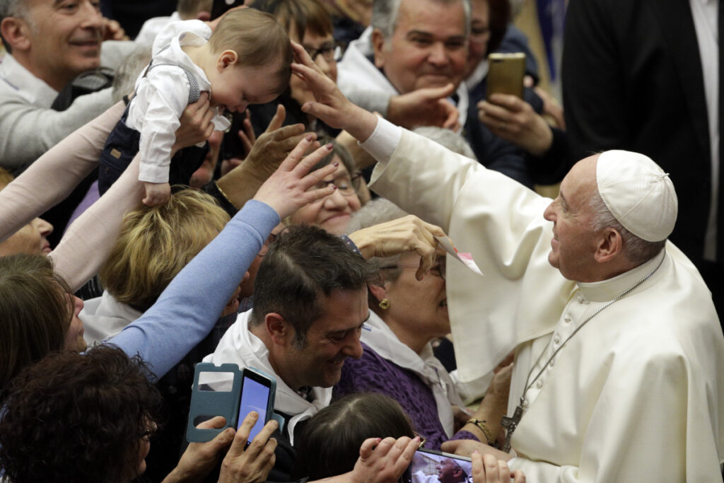 Pope Francis blesses a child while greeting members of a youth tourism group in the Paul VI Audience Hall at the Vatican on Friday.