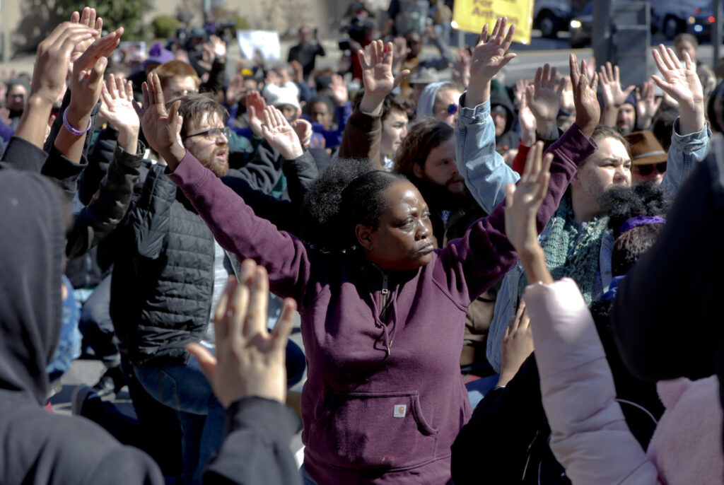 Marchers stop and sit with their hands up in an intersection in the streets Saturday in Pittsburgh.