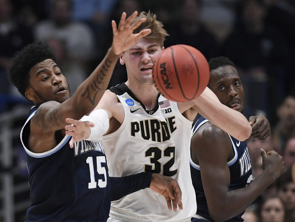 Villanova's Saddiq Bey, left, Purdue's Matt Haarms, center, and Villanova's Dhamir Cosby-Roundtree, right, vie for a loose ball during the first half of Saturday's game in Hartford, Conn.