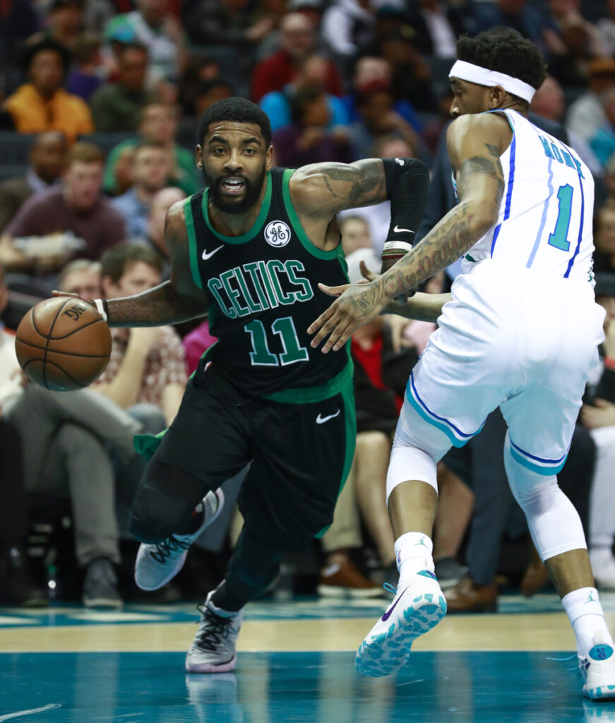 Celtics guard Kyrie Irving moves past Charlotte's Mailik Monk during Boston's 124-117 loss Saturday in Charlotte, North Carolina. The Celtics blew an 18-point fourth-quarter lead and were outscored by the Hornets 30-5 in the final 8:21.