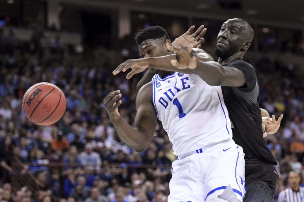 Central Florida center Tacko Fall defends Duke forward Zion Williamson during their second-round game Sunday in Columbia, South Carolina.