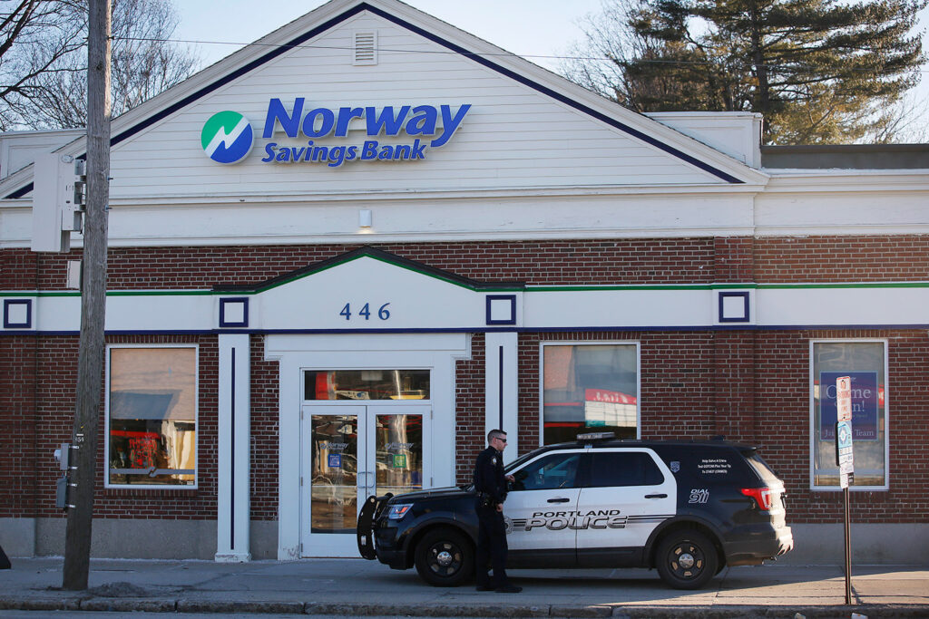 A Portland police crusier sits in front of the Norway Savings Bank branch on Forest Avenue after an armed robbery there on Monday afternoon.