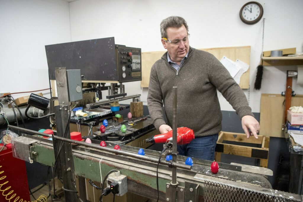 Michael Conway, director of marketing and sales at Maine Wood Concepts in New Vineyard, explains the painting process Friday on the Easter egg production line.
