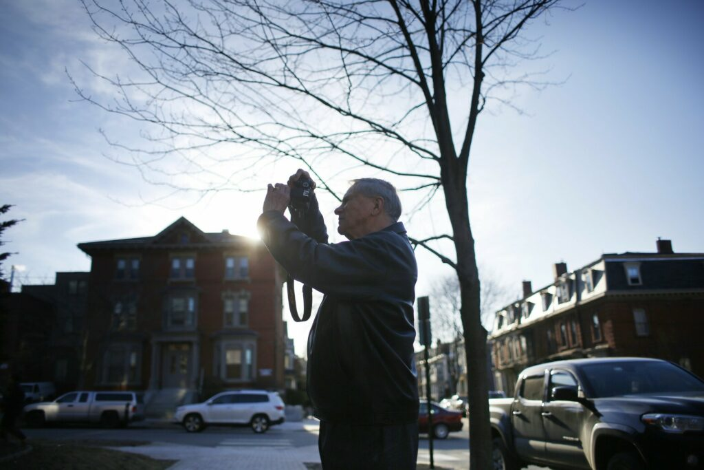 Ronald Perreault takes a photograph of the building where the car he was found in was parked on Deering Street in Portland.