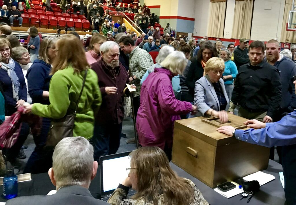 Gov. Janet Mills, right center, casts her ballot along with other Farmington residents who voted on whether to support the NECEC project at the annual Town Meeting on Monday. The vote was 262-102 to oppose the project.