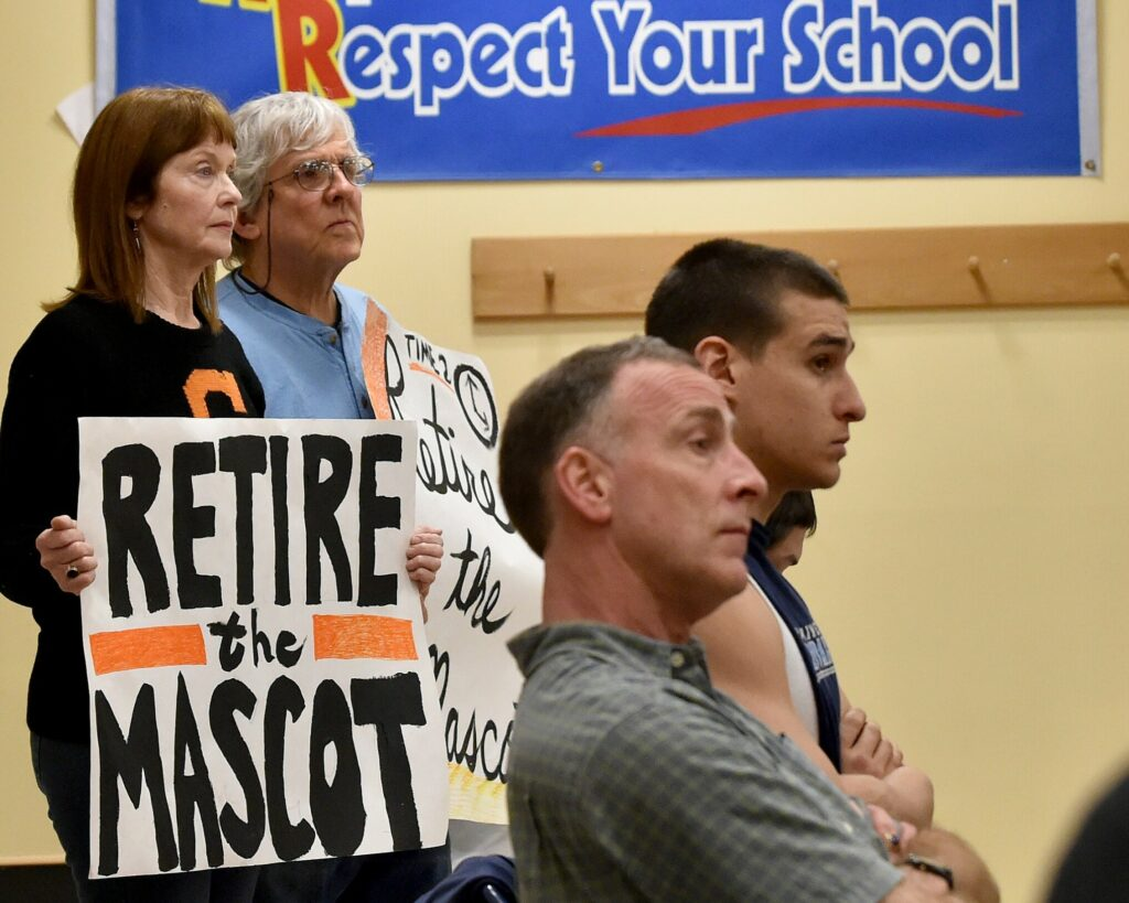 Linda Savage, back left, and Mark Roman, back center, stand with signs calling for the Skowhegan Area High School Indian mascot be retired during an April 7, 2016, School Administrative District 54 board meeting at Skowhegan Area Middle School.