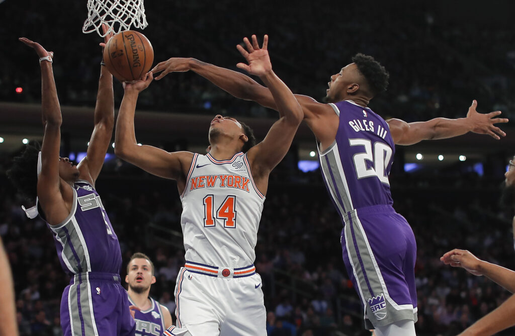 New York Knicks guard Allonzo Trier puts up a shot against Sacramento Kings forward Harry Giles III, right, and guard De'Aaron Fox during the Kings' 102-94 win Saturday in New York.