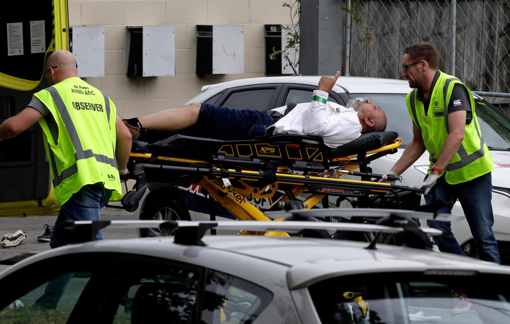 Ambulance workers take a man from outside the mosque in Christchurch, New Zealand, where a witness said many people were killed Friday in a mass shooting.