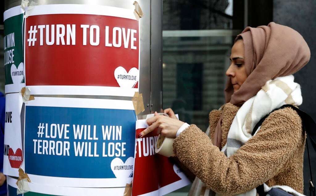 "A demonstrator hangs banners from multi-faith group 'Turn to Love' during a vigil at New Zealand House in London, Friday, March 15, 2019. Multiple people were killed in mass shootings at two mosques full of worshippers attending Friday prayers on what the prime minister called ""one of New Zealand's darkest days,"" as authorities detained four people and defused explosive devices in what appeared to be a carefully planned attack."