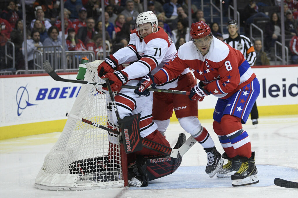 Alex Ovechkin of the Caps battles with Carolina's Lucas Wallmark and goaltender Petr Mrazek in the second period Tuesday night.