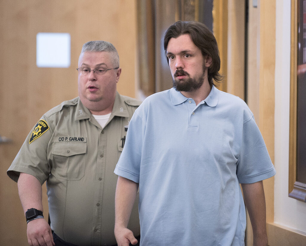 John De St. Croix is escorted into the courtroom at the Penobscot Judicial Center in Bangor in May. De St. Croix, a homeless man, was convicted Friday of setting fire to a delivery truck and killing two other transients who'd been sleeping inside in Bangor. De St. Croix showed no emotion as the jury found him guilty of murder and arson.