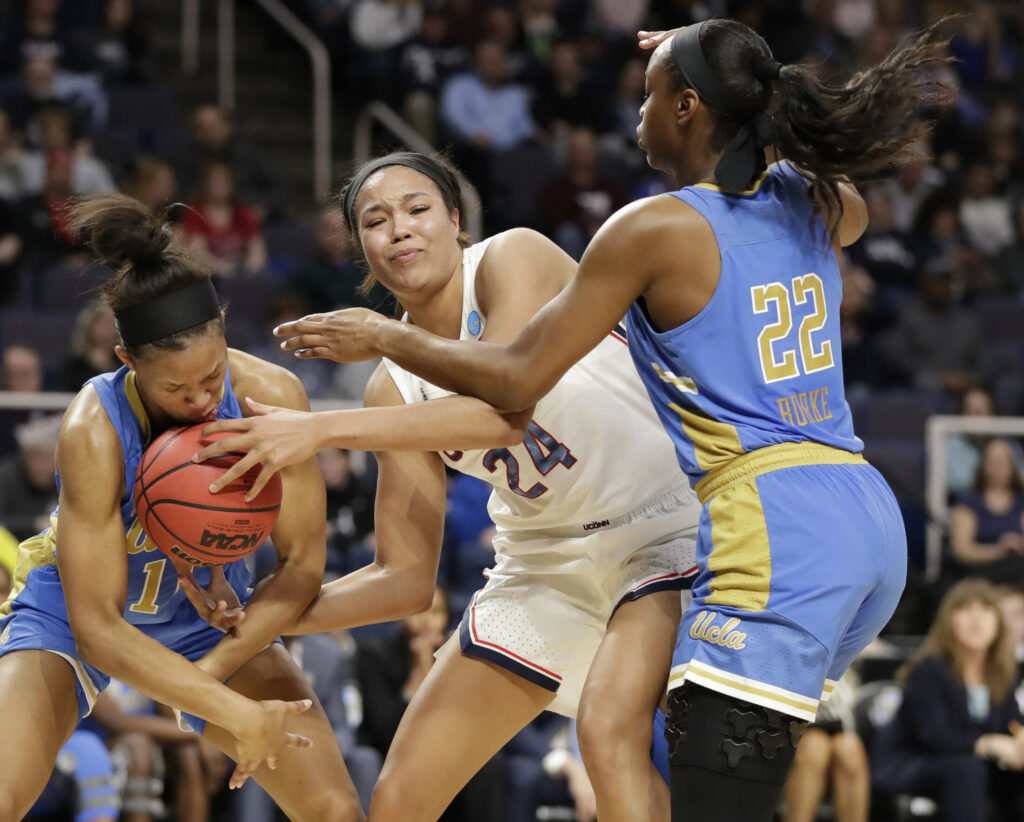 UCLA's Lajahna Drummer, left, gets hit with the basketball as she tries to steal the ball from UConn's Napheesa Collier with UCLA guard Kennedy Burke defending in the first half Friday night at Albany, N.Y. Associated Press/Kathy Willens