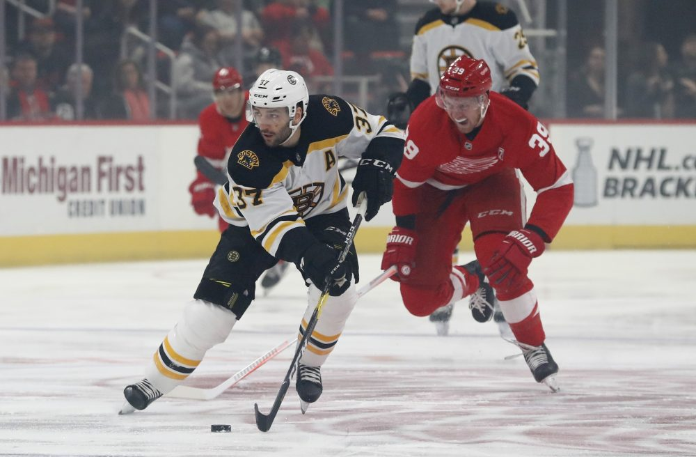 Boston's Patrice Bergeron controls the puck as Anthony Mantha of the Red Wings chases during the first period Sunday night in Detroit. Mantha scored three goals in a 6-3 victory.