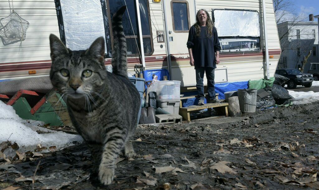 Lana Stafford and her cat outside the camper where she resides in Augusta. The Augusta City Council is scheduled to discuss prohibiting residing in campers year-round in the city.