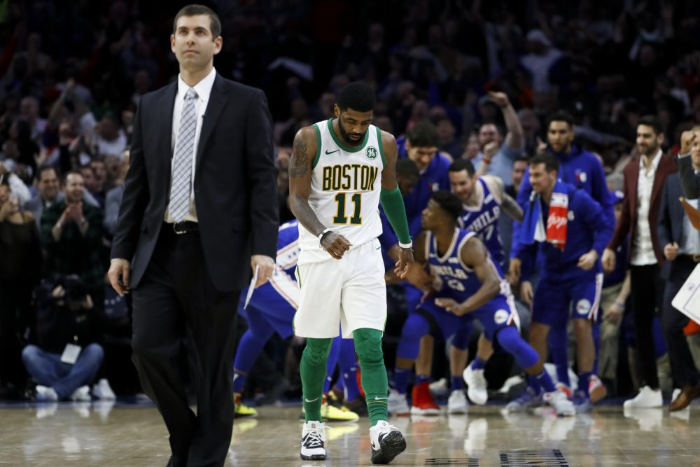 Boston Celtics' Kyrie Irving, center, and coach Brad Stevens, left,  walk the court for a timeout after Jimmy Butler scored a basket during the second half of an NBA basketball game Wednesday, March 20, 2019, in Philadelphia. Philadelphia won 118-115. (AP Photo/Matt Slocum)