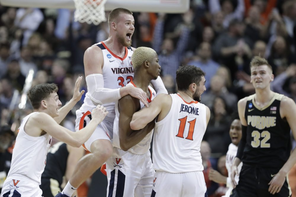 Virginia's Jack Salt (33) celebrates with teammates Mamadi Diakite and Ty Jerome (11) after Diakite hit a shot to send the South Regional final into overtime on Saturday in Louisvile, Kentucky. Virginia won 80-75 to reach the Final Four for the first time since 1984.