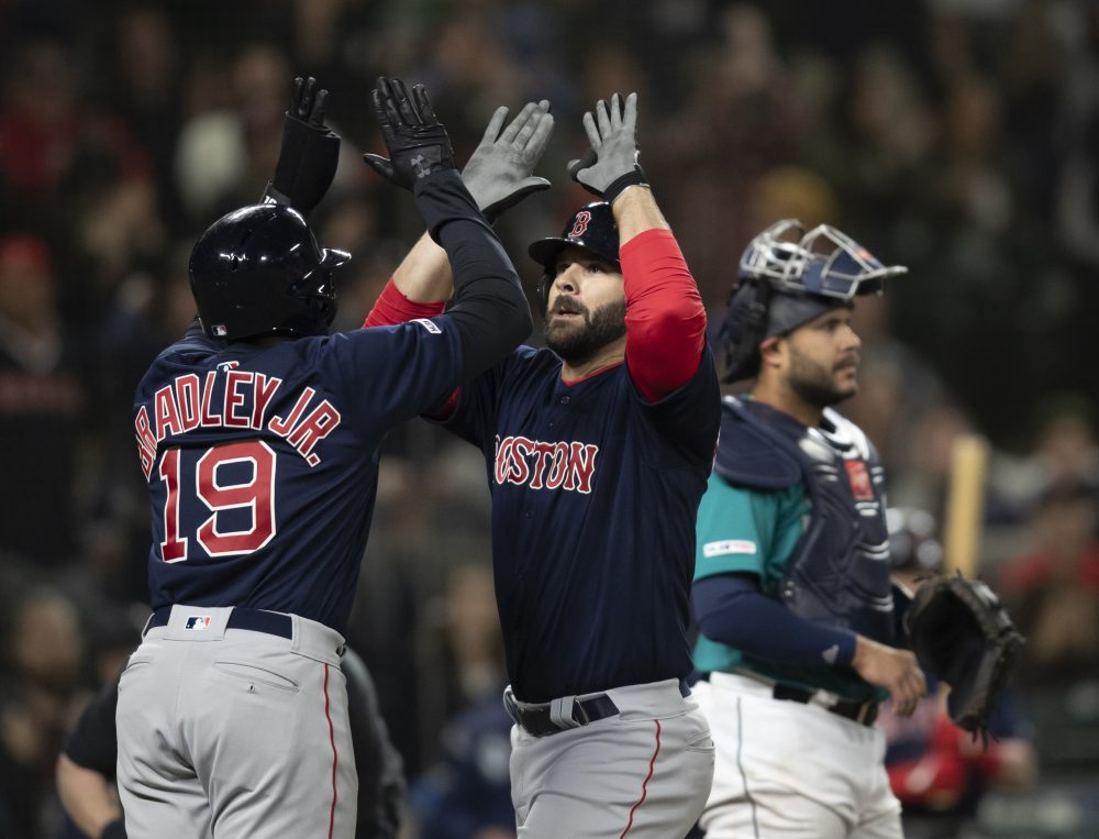 Boston Red Sox's Mitch Moreland, center, is congratulated by Jackie Bradley Jr., after hitting a three-run home run off of Seattle Mariners Hunter Strickland during the ninth inning of a baseball game Friday, March 29, 2019, in Seattle. (AP Photo/Stephen Brashear)