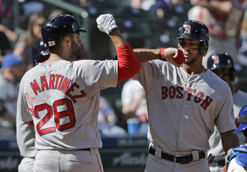 Xander Bogaerts, right, greets J.D. Martinez after Martinez hit a three-run homer Sunday in Seattle. Bogaerts reportedly is nearing a six-year extension with the Red Sox.