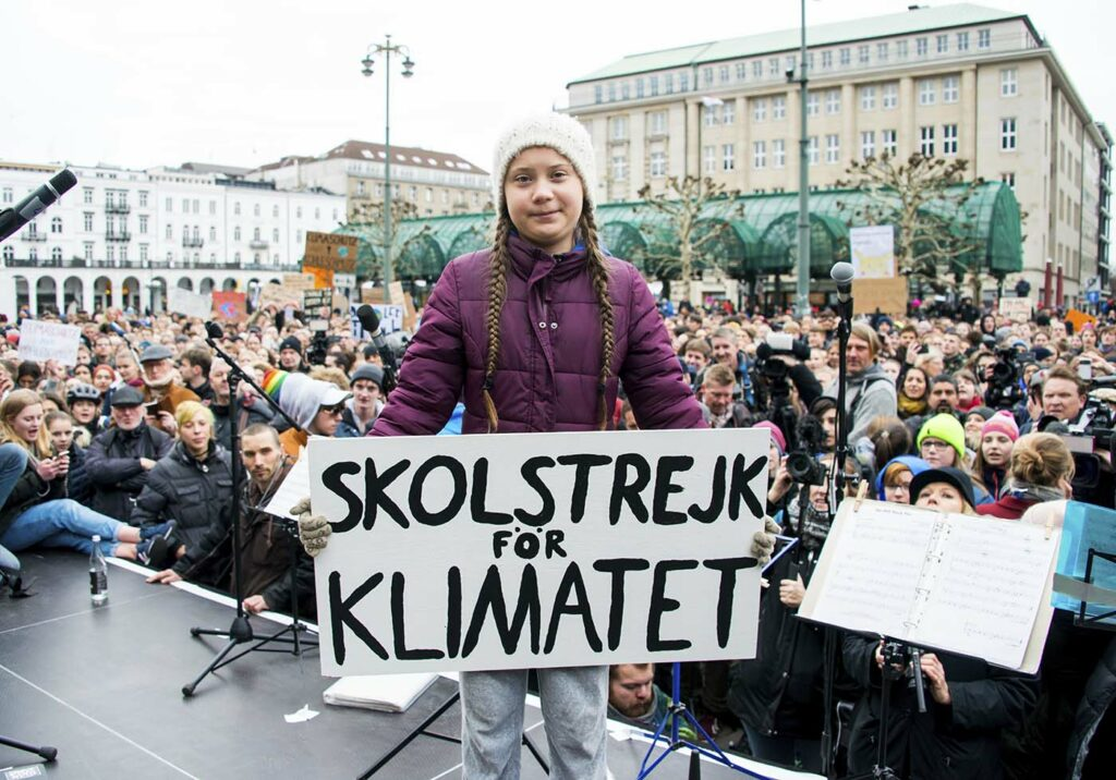 Swedish climate activist Greta Thunberg holds a protest poster as she attends a protest rally in Hamburg.