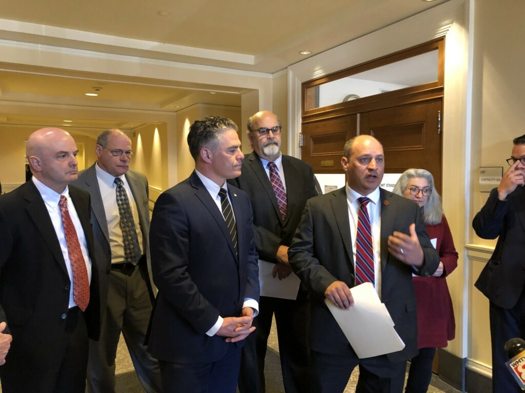 Portland Mayor Ethan Strimling, left center, and Auburn Mayor Jason Levesque, right center, address reporters at the State House on Wednesday about a bill that would allow cities and towns to create a local sales tax.