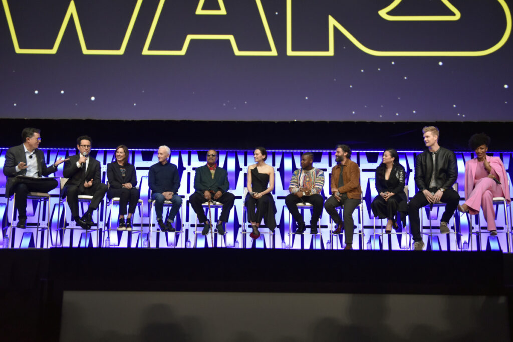"""Stephen Colbert, from left, J.J. Abrams, Kathleen Kennedy, Anthony Daniels, Billy Dee Williams, Daisy Ridley, John Boyega, Oscar Isaac, Kelly Marie Tran, Joonas Suotamo and Naomi Ackie participate in the """"Star Wars: The Rise of Skywalker"""" panel on day 1 of the Star Wars Celebration at Wintrust Arena on Friday, April 12, 2019, in Chicago. (Photo by Rob Grabowski/Invision/AP)"""