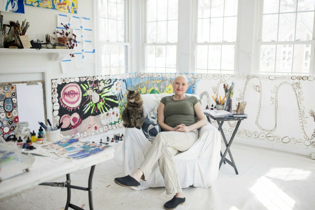 Erin McGee Ferrell, with her cat, Milo, in her studio at home in Falmouth. McGee Ferrell was diagnosed with breast cancer and is currently going through chemotherapy treatments. She has created a series of paper dolls with names like Ms. Mastectomy and Ms. Radiation as an educational series to help women navigate their cancer treatments.
