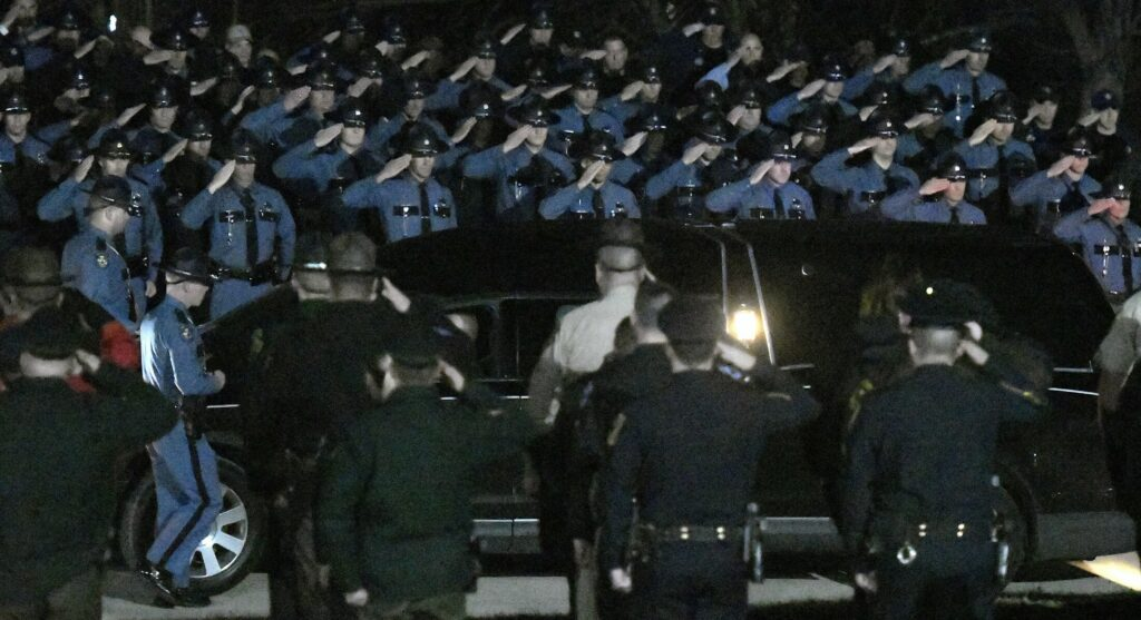 Troopers salute Wednesday evening as the body of Maine State Police Detective Benjamin Campbell is escorted to the Medical Examiner's Office in Augusta. Campbell was killed Wednesday morning in a freak accident on Interstate 95 in Hampden.