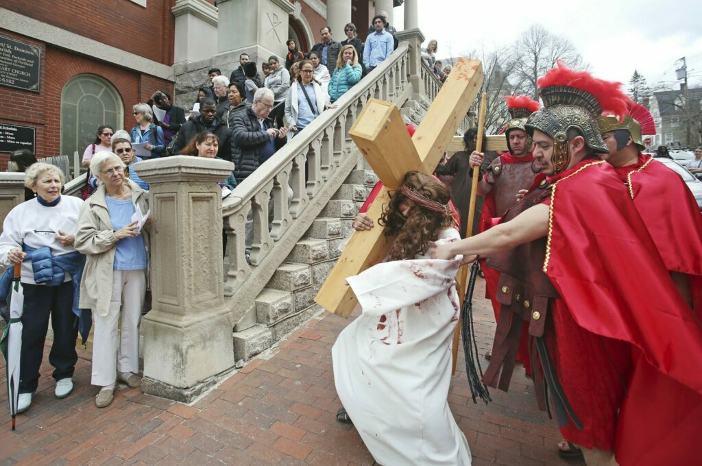 Parishioners of Sacred Heart Church in Portland watch as Cesar Lopez portrays Jesus and others portray Roman soldiers as part of Good Friday observances. The group reenacted the Stations of the Cross, which are a Roman Catholic devotion that depicts events on Jesus Christ's last day, from his condemnation to his crucifixion. Here, he carries his cross.