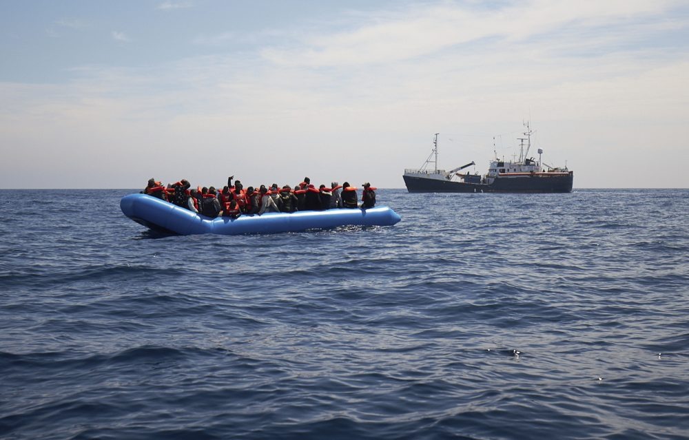Migrants on a rubber dinghy are approached by the Sea-Eye rescue ship in the waters off Libya on Wednesday.