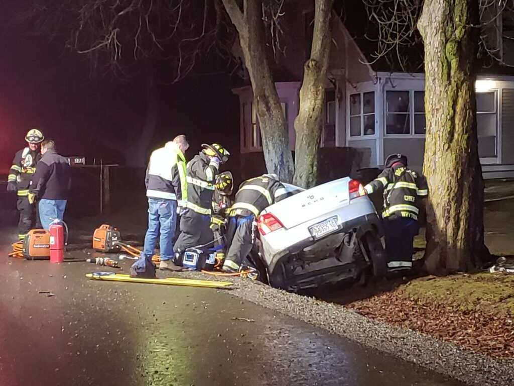 Rescue crews work to get the driver of a car out of the wrecked vehicle.