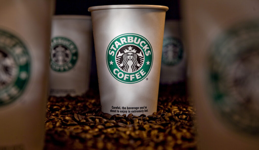 Chains like Starbucks want better cups than the plastic lined, plastic-lidded ones in use now.