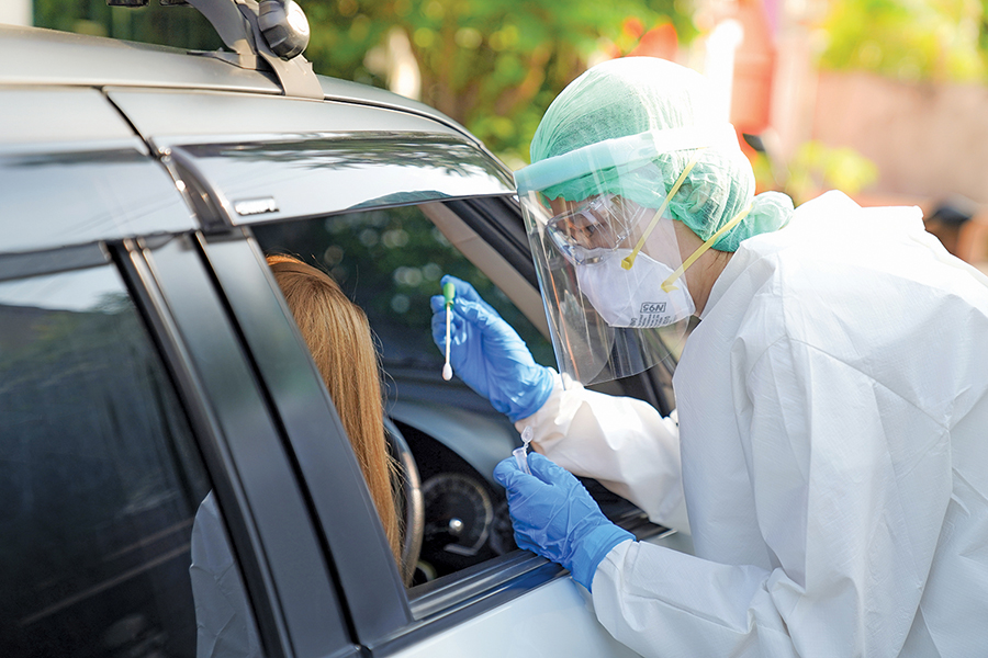 A patient is tested for COVID-19 in their vehicle at a drive-through testing site.