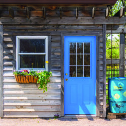 A garden shed with a blue door that is used for more than storing lawn care equipment.