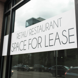 A banner in a window advertising commercial retail and restaurant space for lease