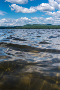 Photo taken close to the surface of the luscious water of Sebago Lake, looking west toward the mountains on a sunny day.