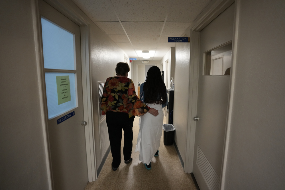 A 33-year-old mother of three from central Texas is escorted down the hall by clinic administrator Kathaleen Pittman before getting an abortion Saturday at Hope Medical Group for Women in Shreveport, La.