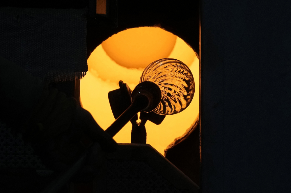 A glassblower heats an artistic creation in a methane-powered oven on Murano island, Venice, Italy, on Thursday.