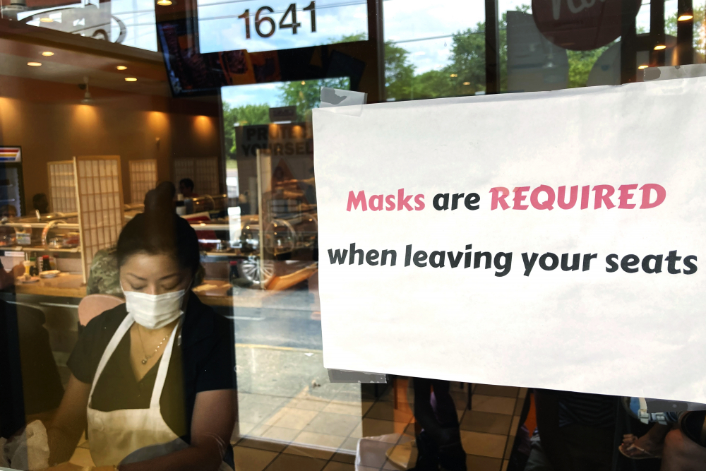 A sign requiring masks is displayed at a restaurant in Rolling Meadows, Ill.  Nam Y. Huh/Associated Press, file