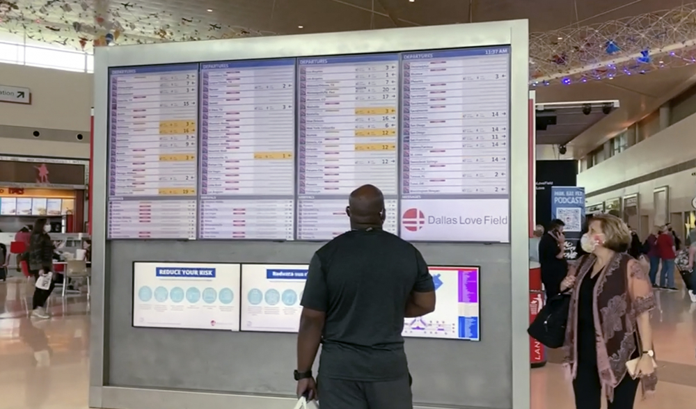 Passengers look for information on their flights Sunday at Dallas Love Field.